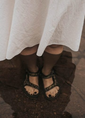 Girl waring sandals with her feet under water